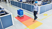 A man crosses the path of an automated guided vehicle in a production facility and is reliably detected.